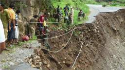 Rescuers helping people cross damaged roads on foot with the help of ropes