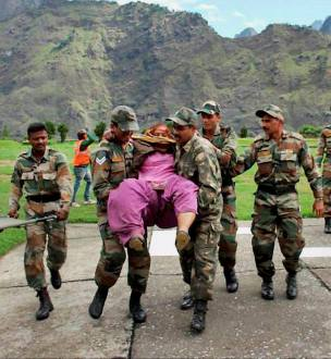 Army personnel rescue a woman pilgrim at flood-hit Hemkund in Chamoli district.