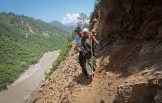 A pilgrim is helped by a villager as she tries to cross on a pathway damaged by landslide in Rudraprayag in the Himalayan state of Uttarakhand June 20, 2013.