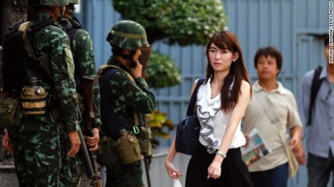 Thai office workers walk past armed soldiers standing guard outside the Shinawatra Tower Two in Bangkok, Thailand, 20 May 2014. Thai army Chief Prayuth Chan-ocha early on 20 May 2014, declared martial law giving the military full control to prevent further protest-related violence in the country. The statement was issued about 3 am on 20 May (2000 GMT), according to local media reports. Prayuth has the authority to declare martial law without the consent of the government, which has had caretaker status since 09 December 2013. Thailand has been wracked by six months of non-stop protests seeking to topple the government. At least 25 people have died in political-related violence and more than 700 injured.  EPA/NARONG SANGNAK /LANDOV